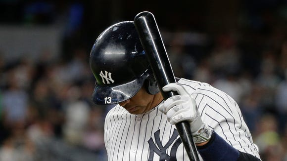New York Yankees' Alex Rodriguez taps his batting helmet with his bat after flying out to left field with two men on base against the Colorado Rockies during the fifth inning of a baseball game, Tuesday, June 21, 2016, in New York.