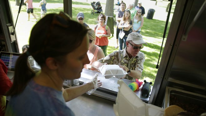Kathy Zobel of Hawg Tyed BBQ hands Dave Sipe his container of food during a food truck rally in Pierce Park.