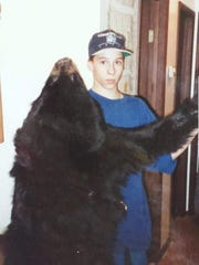 Mathew Poteet at age 14 with a bear he killed earlier