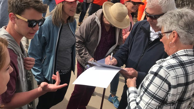 St. George residents sign a petition for volunteers with the Better Boundaries Coalition during a public demonstration on Saturday, March 24, 2018.