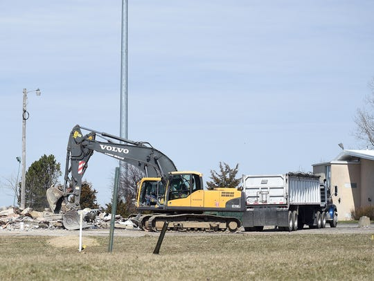 An excavator is used to clear what is left of the former