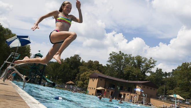 Briana Marsh, 9, leaps into the Gypsy Hill Park pool enjoying the last weekend before school starts on Saturday, Aug. 15, 2015.