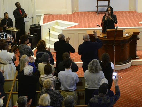 Ilyasah al Shabazz uses her cell phone to snap a picture of the crowd at the First Unitarian Universalist Society church after giving the keynote address at an annual Martin Luther King Jr. Day remembrance in Burlington.