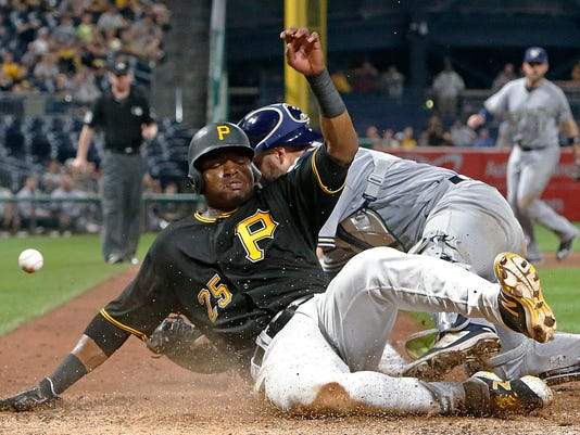 Pittsburgh Pirates' Gregory Polanco (25) scores on a single by Max Moroff as the ball gets away from Milwaukee Brewers catcher Manny Pina during the eighth inning of a baseball game in Pittsburgh, Monday, July 17, 2017. Polanco went 4 for 4 in the Pirates' 4-2 win. (AP Photo/Gene J. Puskar)