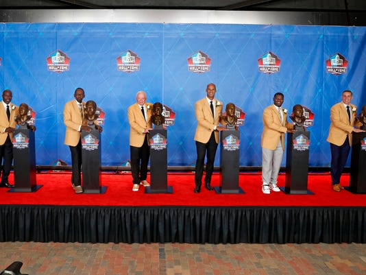 Members of the Pro Football Hall of Fame Class of 2017, minus kicker Morten Andersen, pose with their busts following inductions at the hall Saturday, Aug. 5, 2017, in Canton, Ohio. From left are Terrell Davis, Kenny Easley, Jerry Jones, Jason Taylor, LaDanian Tomlinson and Kurt Warner. Andersen had left before the photo was taken. (AP Photo/Gene J. Puskar)