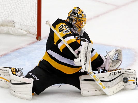 FILE - In this May 13, 2017, file photo, Pittsburgh Penguins goalie Marc-Andre Fleury makes save during the third period of Game 1 of the Eastern Conference final in the NHL Stanley Cup hockey playoffs against the Ottawa Senators in Pittsburgh. The three-time Stanley Cup-winner has departed the Penguins to become the face of Golden Knights after being selected in the NHL expansion draft in June. (AP Photo/Gene J. Puskar, File)