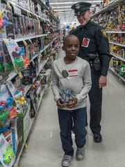 Jayden Crawford and Livonia Officer Dan Moilanen walk the aisles of the Meijer toy department.