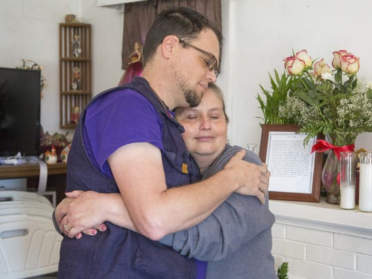 Jason Odhner of Phoenix Allies for Community Health hugs Dora, a patient, during a house call while she prepares for her father's funeral.