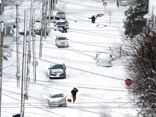 Residents in Erie, Pa. dig out on Dec. 26, 2017, after a record two-day snowfall. The National Weather Service office in Cleveland says the storm brought 34 inches on Christmas Day, a new all-time daily snowfall record for Erie.