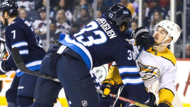 Jets defenseman Dustin Byfuglien (33) checks Predators forward Viktor Arvidsson (38) during the first period March 25 at Bell MTS Place.