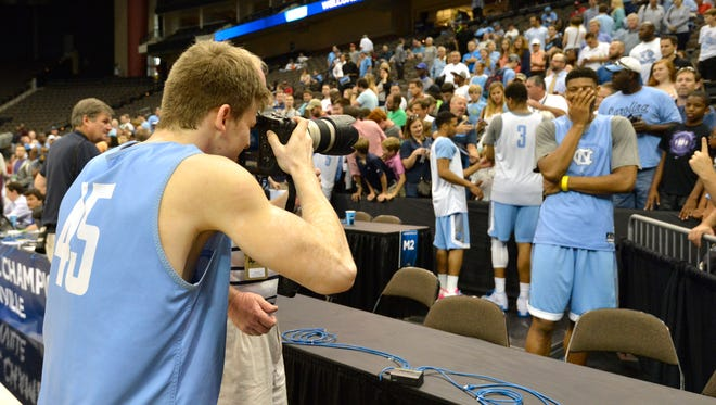 North Carolina Tar Heels guard Stilman White borrows a photographers camera to take a photo of teammate forward Isaiah Hicks following practice before the second round of the 2015 NCAA Tournament at Jacksonville Veteran Memorial Arena.