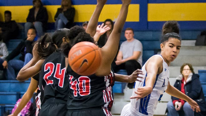 A.I.'s Lauryn Griffin sends a behind-the-back pass past a group of William Penn defenders in the first half of A.I.'s 68-33 win over William Penn at A.I. duPont High School in Greenville on Thursday evening.