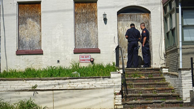 Capt. Demetrius Todd (left) and firefighter James Johnson of the Wilmington Fire Department make note of safety issues at a vacant property on Washington Street.