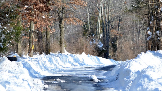 A country road is barely cleared after the blizzard of last week. Wildlife have to deal with the piled up snow, too.