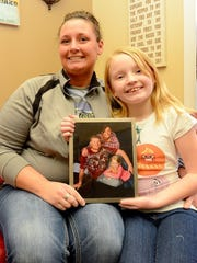 Melanie Newcombe and her daughter Teegan, 9, sit with a portrait of their family Tuesday in Ionia. Newcombe's husband Brandon, a Marine, bought the house for the family to fix up and live in. Brandon died on May 16, 2014, but two Michigan non profits - Faith Works Michigan and Operation: Come H.O.M.E. - teamed up to finish the work on the house.