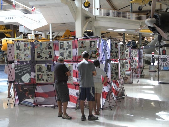 Visitors examine the portraits of fallen service members at the 'Remembering Our Fallen' exhibit.