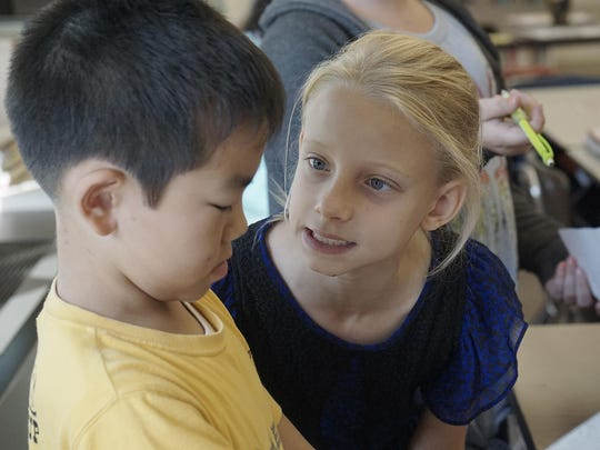 In the 3/4 grade split multicultural classroom run by teachers Chris Michuta and Amy Jackson, Leah Frazier helps Tatsuki Tanimichi learn about the students in his class.