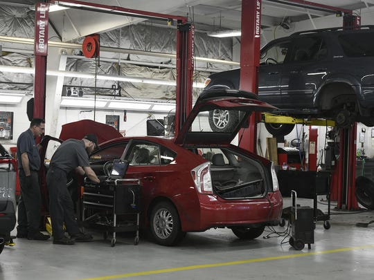 Laurel Toyota mechanics, from left, Rich Grayish and Steve Dunn work on a hybrid car recall on a Toyota Prius at the Johnstown, Pa., Toyota dealership, Friday, March 20, 2020. Pennsylvania Gov. Tom Wolf announced a list of non-essential businesses that are being told to close to contain the spread of coronavirus. Car dealerships are allowed to keep their auto repairs shops open. (Todd Berkey/The Tribune-Democrat via AP)