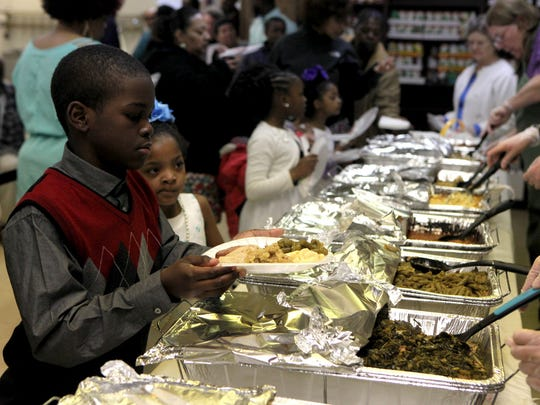 A community Easter meal is served to (from left) Jaquan Wise, 9; his cousin Zyleah Lawrence, 6; sister Tyonia Wise, 8; and Zyleah's twin, Zydaria Lawrence, all of Bridgeton, at Bethany Grace Community Church.