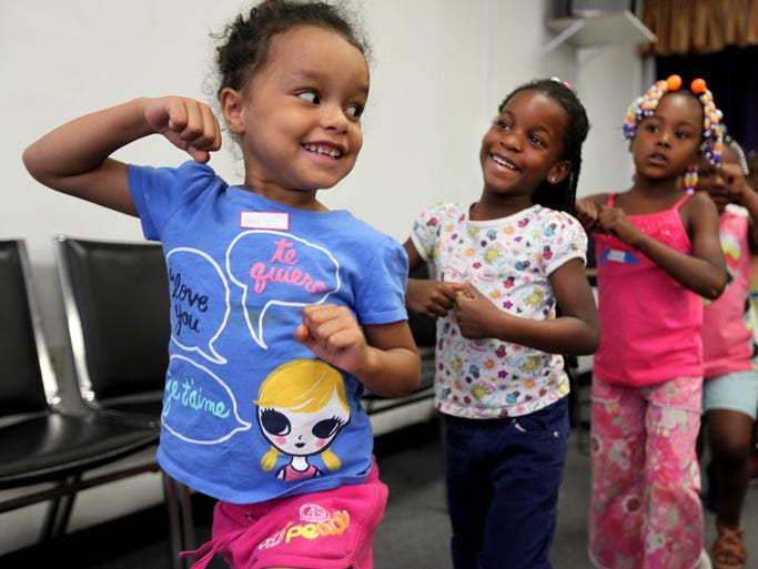 Hailee, 4, leads Clara, 5, and Peninnah, 5, in their House of Hope march during summer camp at the House of Hope Church in Winton Terrace.