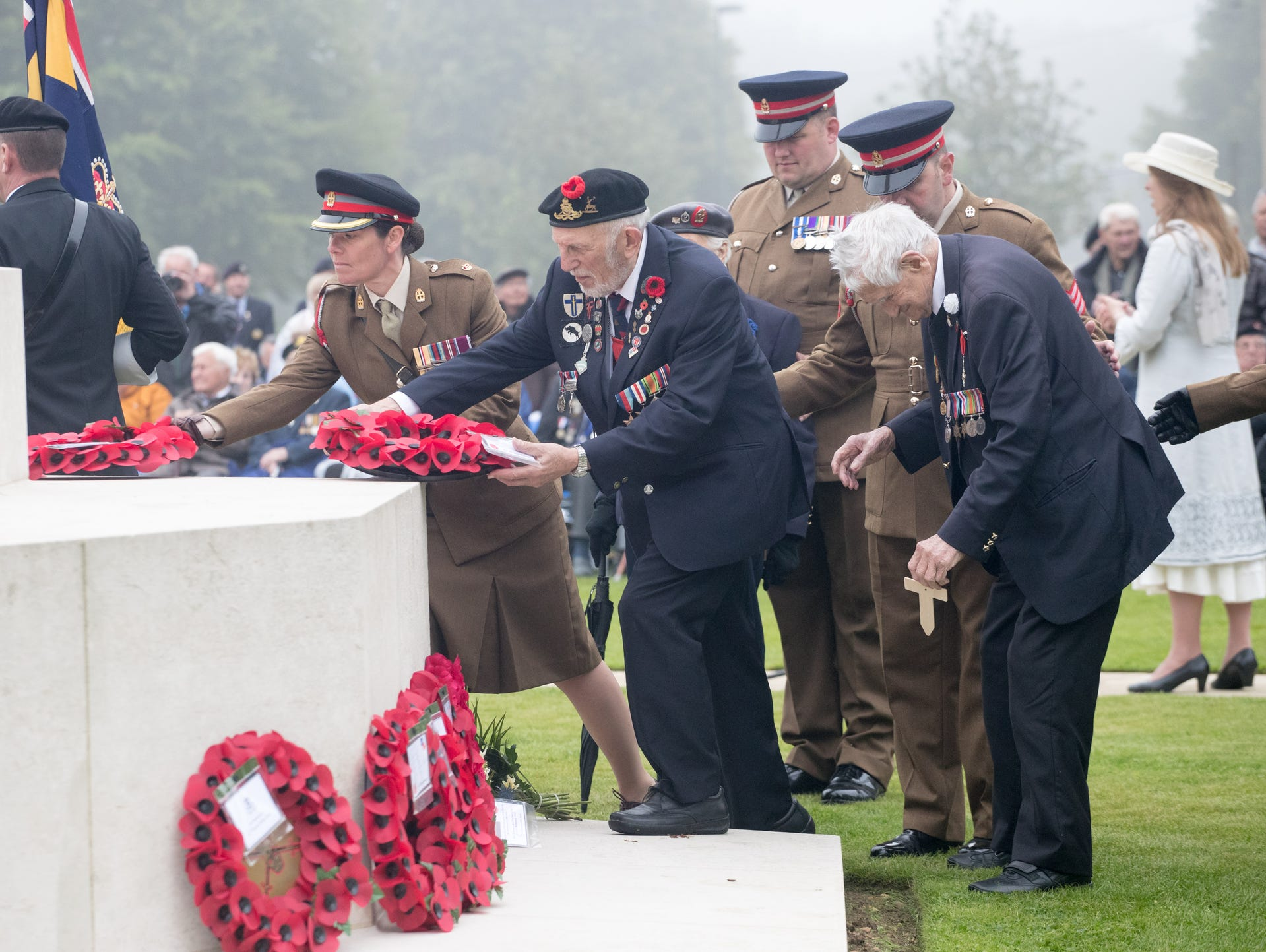 Normandy veterans lay wreaths as they attend an official