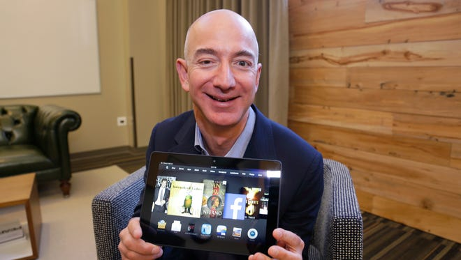 Jeff Bezos, CEO of Amazon.com, holds the 8.9-inch version of the new Amazon Kindle HDX tablet computer in Seattle.
