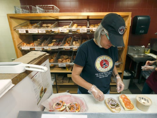 Co-owner Rebecca Maleck prepares sandwiches at Balsam Bagels in the North Winton Village.
