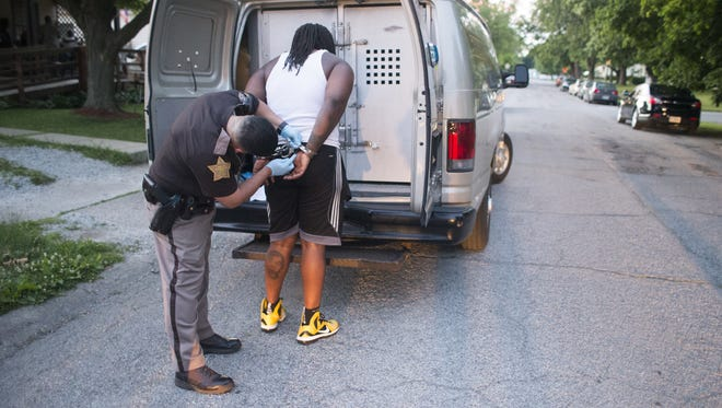A man is placed into custody by Marion County Sheriff's Deputy Jose Sanchez, in the 1600 block of North Irvington, Indianapolis, Saturday, June 18, 2016. IMPD led an interagency effort to serve warrants on a variety of violent and drug-related charges. At least 25 people were arrested and four handguns were recovered in Operation First Step.