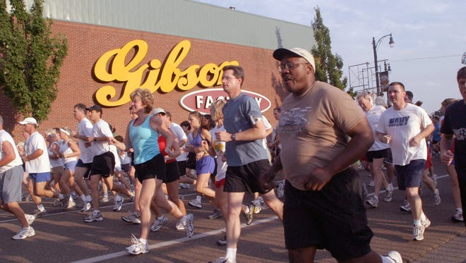 Runners and walkers pass the Gibson Guitar Factory in Downtown Memphis.