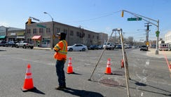 Workers measure manhole covers for possible replacement