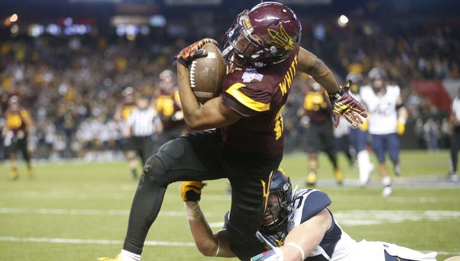 Arizona State wide receiver Tim White avoids being tackled by West Virginia linebacker Nick Kwiatkoski to score a touchdown during the third quarter of the Cactus Bowl at Chase Field in downtown Phoenix on Saturday. West Virginia won, 43-42.
