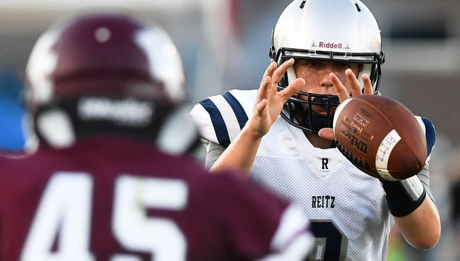 Reitz Panther quarterback Reid Mahan takes a snap under defense from Henderson's Ian Pitt as the Henderson County Colonels host the Reitz Panthers for the Hall of Fame game at Colonel Stadium Friday. The matchup is the first game of the season for both teams, August 19, 2016.