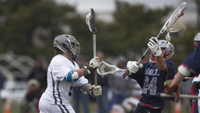Manasquan's Canyon Birch (left) tries to shoot past Wall's Sean DeMott during first half action. Manasquan defeated Wall, 19-7, in Class B South Boys Lacrosse game in Sea Girt, NJ on April 19, 2017