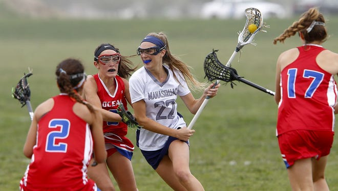 Manasquan's Janie Cowley (#22) moves down the field through Ocean defenders during their game at the National Guard Training Center in Sea Girt Thursday, April 27, 2017.