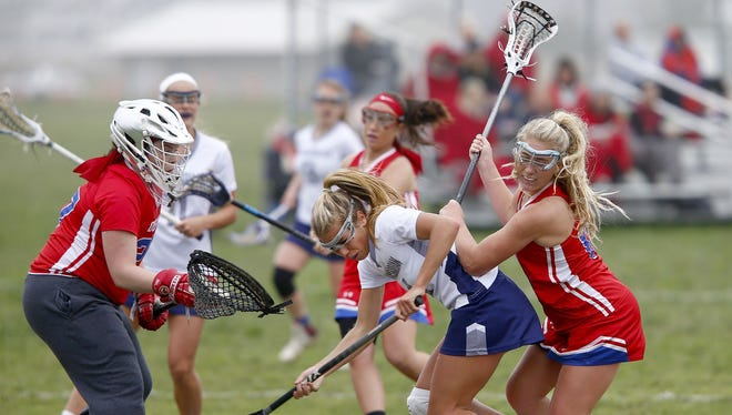 Ocean's Talia Pritzlaff (right) and Manasquan's Logan Harms (center) battle for the ball in front of Ocean goalie Shannon Ross during their Class B North game at the National Guard Training Center in Sea Girt Thursday, April 27, 2017.