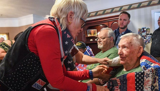 Marion Mockridge, left, places a quilt on the back of T.L. Herron, an Army Veteran who served in Korea, during a Veteran's Day celebration at Morningside Assisted Living in Anderson on Friday. A group of 11 veterans were given a hand-made blanket from the South Carolina Quilts of Valor group of Anderson. The group has given them to nearly 250 veterans this year.
