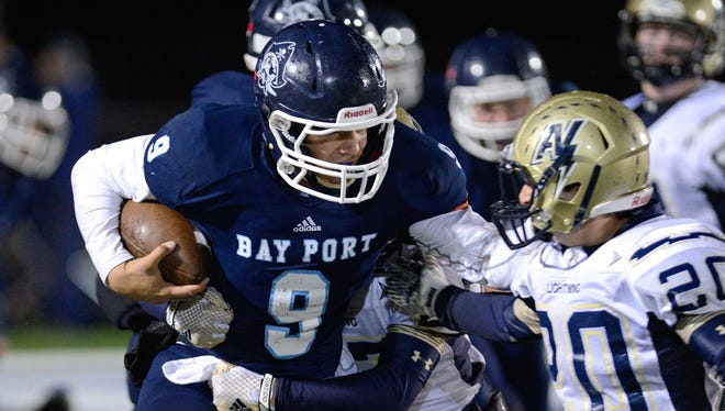Bay Port quarterback Alec Ingold stiff-arms Appleton North defensive back Hunter Rolain during the second quarter in a WIAA quarterfinal playoff game in Suamico.