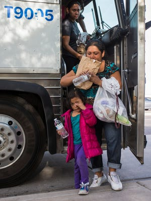 Migrants get off a federal bus on Monday at the Greyhound station in Phoenix. Undocumented immigrants from Central America, transferred from Texas, have been released in Arizona since last week.