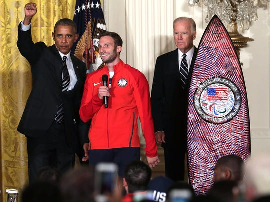 U.S. President Barack Obama gestures as he is presented with a Team USA surfboard by Olympian Josh Brunais.