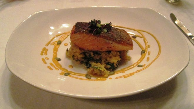 Salmon placed on a bed of chieftain quinoa, acorn squash, baby spinach and pumpkin seed vinaigrette at the Wisconsin Room of the American Club in Kohler.