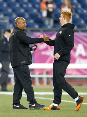 Cincinnati Bengals offensive coordinator Hue Jackson greets Cincinnati Bengals quarterback Andy Dalton (14) before the start of their game against the New England Patriots played at Gillette Stadium in Foxborough, Massachusetts Sunday October 5, 2014.