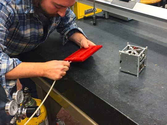 Alex Golden, a senior mechanical engineering student at UVM, prepares to test the propulsion system for small satellites developed by GreenScale Technologies.