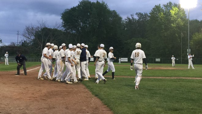DeWitt players celebrate at home plate after Will Nagel's home run gave the Panthers a 5-4 lead over Okemos in the third inning on Thursday night.