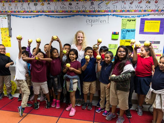 Mary Eckard poses for a photo with her first-grade students  after she received a Golden Apple award at Highlands Elementary in Immokalee on Friday, Feb. 23, 2018.