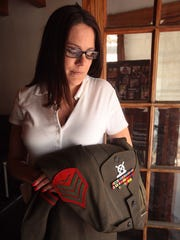 Genevieve Scahill holds her husband's service dress uniform at her Bellflower home on May 9, 2013. Her husband, Marine Sgt. Martin Scahill, killed himself in the couple's backyard on April 5, 2010.