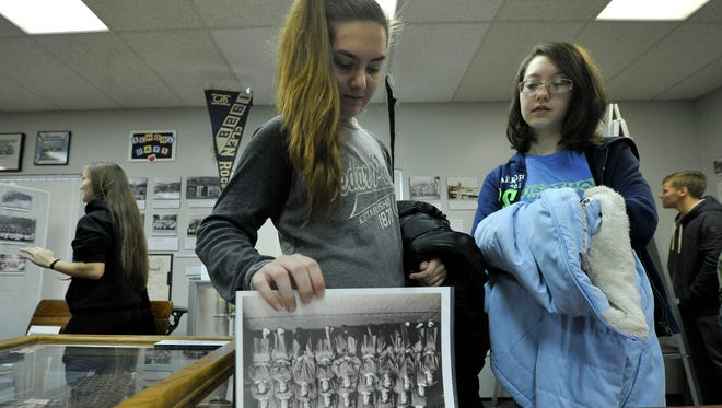 Kate Cramer, left, and Angelica Hunt, looks through the photographs and articles from the Glen Rock Item, during a visit by Susquehannock High School students to the Glen Rock Museum.