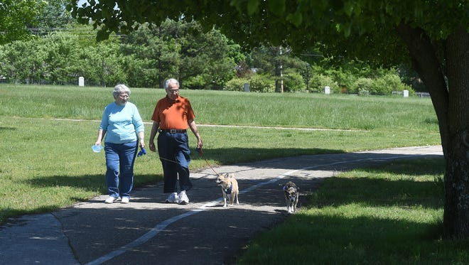 Kathy Crane, 73, and Tom Crane, 74, of Mountain Home, walk their dogs, Dickens and Snuggles, at Copper Park on Thursday. Kathy said the park is a big part of her fitness regiment. A recent report ranking a county's health showed access to fitness programs, and healthy areas like parks, play a factor in a county's overall health.