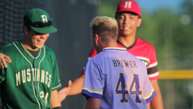 Bishop Brossart senior Trent Parker and Holmes senior DV Gulley greet Campbell County senior Noah Brewer after Brewer tripled and scored on an error during the NKBCA senior all-star baseball game June 25, 2018 at Dixie Heights HS.. The West won 12-11.