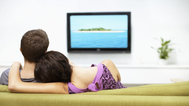 Stock photo of young couple watching television.