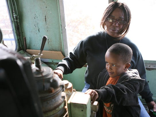 Camyrn Pullen, 3, explores the inside of a train engine
